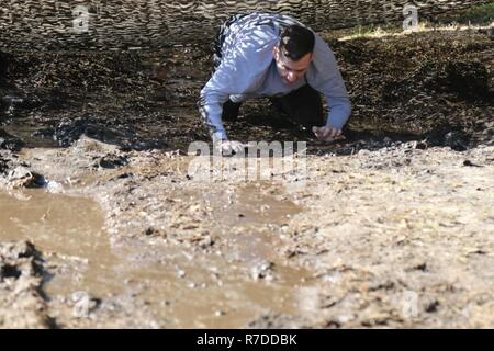 Sgt. Seth Langley, Division Headquarters and Headquarters Battalion, 3rd Infantry Division, crawls out of a mud pit Dec. 4 at Fort Stewart, Ga. as part of the Marne Mudder competition for Marne Week. Every year, 3ID celebrates Marne Week in order to recognize the achievements of Dog Face leaders, Soldiers and Families. This year, the Marne Division celebrated the 100th anniversary of the Battle of the Marne- the historic World War I battle where the division adopted their moniker of the 'The Rock of the Marne'. - Stock Photo