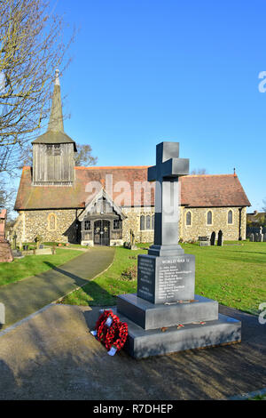 Copy space on blue sky view English village church of England religion with tower & porch poppy wreath war memorial Doddinghurst Brentwood Essex UK