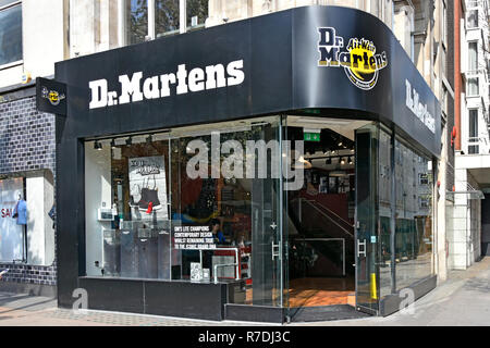 Dr Martens or Doc Martens footwear shoemaker & clothing brand shoe shop front window of store selling shoes boots in Oxford Street London England UK - Stock Photo