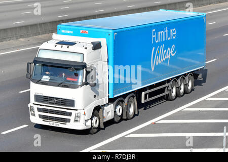 White hgv juggernaut lorry truck driver & blue Furniture Village articulated supply chain transportation trailer driving along motorway England UK - Stock Photo