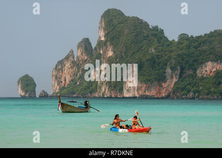 People kayaking at Ao Loh Dalum on Phi Phi Don Island, Krabi Province, Thailand. Koh Phi Phi Don is part of a marine national park. - Stock Photo