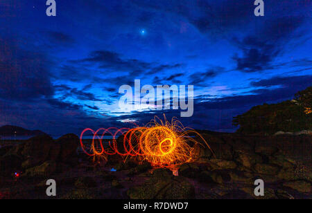 cool burning steel wool fire work photo experiments on the rock at sunrise. - Stock Photo