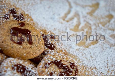 Traditional German hazelnut biscuits with chocolate topping on a wooden board covered with powdered sugar, shape of Christmas tree, Christmas cookies - Stock Photo