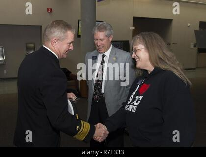 SPOKANE, Washington (May 16, 2017) Rear Adm. Kevin Kovacich, from Spokane, Director of Plans and Policy (J5), U.S. Cyber Command, exchanges challenge coins with Deana Sleep, Veterans Services Program Coordinator and Dr. Ryan Carstens, President of Spokane Community College, during a Navy meet and greet event at Spokane Community College for Spokane Navy Week. Since 2005, the Navy Week program has served as the Navy's principal outreach effort into areas of the country without a significant Navy presence, with 195 Navy Weeks held in 71 different U.S. cities.  The program is designed to help Ame - Stock Photo