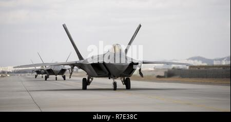 F-22 Raptors from Joint Base Elmendorf-Richardson, Alaska, taxi for takeoff at Gwangju Air Base, Republic of Korea, Dec. 04, 2017. The fighter aircraft are participating in the pinensula-wide routine exercise, Vigilant Ace-18. - Stock Photo