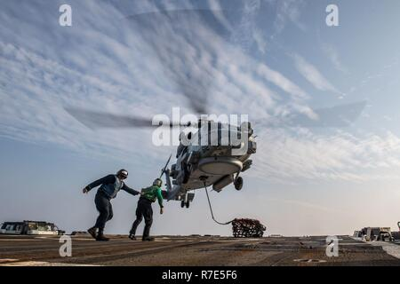 "RED SEA (Nov. 29, 2018) Fire Controlman 2nd Class James Leonard, left, guides Aviation Electronics Technician 3rd Anthony Javarone away from an MH-60R Sea Hawk helicopter, assigned to the ""Vipers"" of Helicopter Maritime Strike Squadron (HSM) 48, during a vertical replenishment exercise aboard the Arleigh-Burke class guided-missile destroyer USS Jason Dunham (DDG 109). Jason Dunham is deployed to the U.S. 5th Fleet area of operations in support of naval operations to ensure maritime stability and security in the Central Region, connecting the Mediterranean and the Pacific through the western In - Stock Photo"