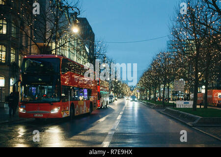 Berlin, December 25, 2017: Beautiful view of the decorated street and the road in Berlin during the Christmas holidays. On the side are tourist buses for sightseeing tourists. - Stock Photo