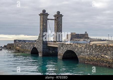 Castle of Saint Gabriel (Castillo de San Gabriel) and the bridge with Castle Doors Puente de Las Bolas on a small island in Atlantic in Arrecife - Stock Photo