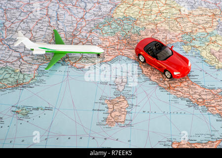 Toy plane and red car on the geographical map of Europe. Travel route planning concept. - Stock Photo