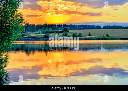 Evening landscape screensaver on the lake with the reflection in the water of the evening sky filled with sun. Background. - Stock Photo