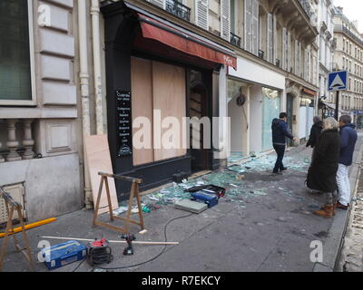Paris, France. 9th Dec 2018. Passers-by watch the destruction of shop windows on Avenue Marceau in the 8th district of Paris, one day after the Yellow West demonstrations. The protest movement of the 'yellow vests' had formed in mid-November in view of planned tax increases on fuels. Meanwhile, the demands go much further. (to dpa 'More than 1700 arrests at 'yellow jackets' demonstrations in France') Photo: Christian Böhmer/dpa Credit: dpa picture alliance/Alamy Live News - Stock Photo