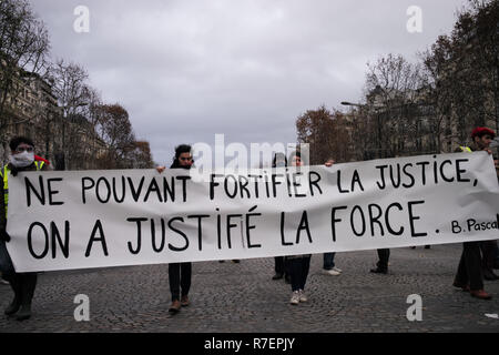 Paris, France. 8th Dec 2018. Demonstrators are walking on the Avenue, showing their sign 'Not able to reinforce justice, we justify force, Blaise Pascal'. Credit: Roger Ankri/Alamy Live News - Stock Photo