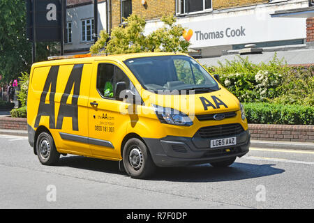 Ford Transit AA van & driver with logo on yellow breakdown van driving along town centre shopping high street in Brentwood Essex England UK - Stock Photo