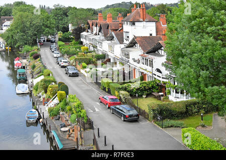 Looking down from above small boats moored on River Thames close to riverside house & car parking on private road Taplow Buckinghamshire England UK - Stock Photo