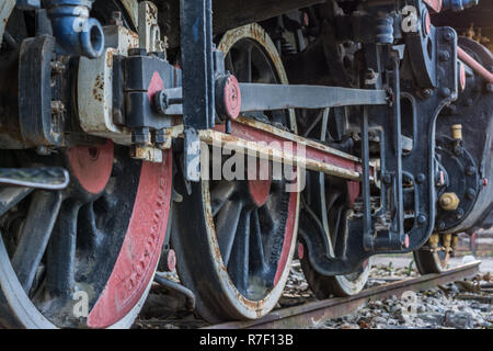 Close-up wheels and parts of vintage steam train locomotive on track - Stock Photo