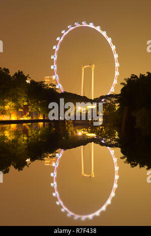 Singapore Flyer reflecting in the water at night, Singapore - Stock Photo