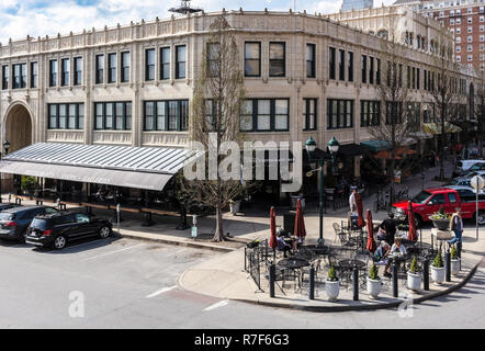 Tourists walk in front of The Grove Arcade in the Downtown Asheville Historic District, the Battery Park Apartments building seen behind it. - Stock Photo