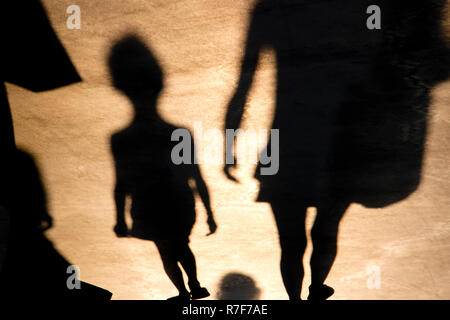 Blurry shadow of a child and mother walking on promenade in summer sunset - Stock Photo