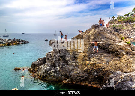 Cinque Terra, Italy - May 18th 2018 - Tourists having fun jumping from the rocks into the sea in Cinque Terra in a hot summer day in Italy - Stock Photo