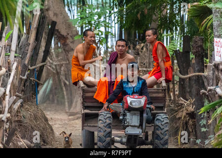 Don Daeng, Laos - April 27, 2018: Young buddhist monks sitting on a tractor surrounded by forest on a remote rural island on the Mekong river - Stock Photo