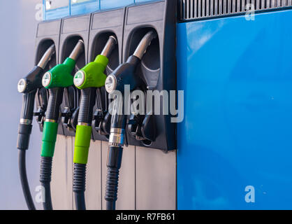 Different Fuel pistols at european Petrol station. 95,98,DD fuel pistols. Focus on the diesel DD & B7 pistol. - Stock Photo