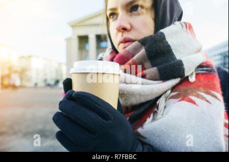 Young beautiful girl in gloves and in a large cozy scarf holding a paper cup of takeaway coffee in urban environment. Coffee to go in winter concept - Stock Photo