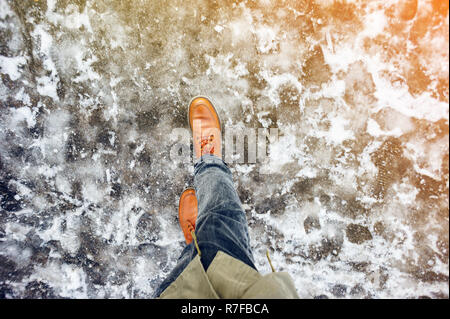 Walk on wet melted ice pavement. First person view on the feet of a man walking along the icy pavement. Pair of shoe on icy road in winter. Abstract e - Stock Photo