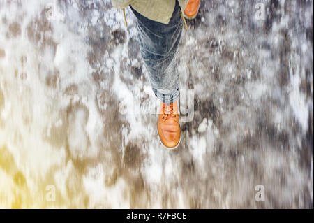 Walk on wet melted ice pavement. View from above on the feet of a man walking along the icy pavement. Pair of shoe on icy road in winter. Abstract emp - Stock Photo