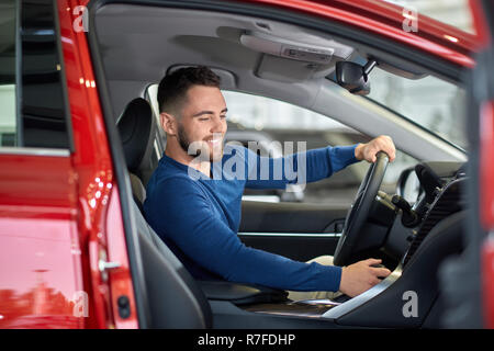 Young driver in blue sweater sitting in luxury car with opened door. Handsome man with beard holding one hand on steering wheel and other on gearbox.  - Stock Photo