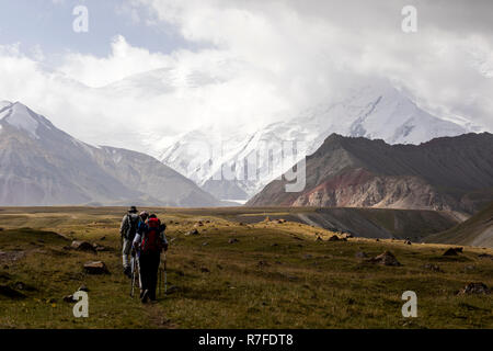 Tulpar, Kyrgyzstan August 21 2018: Tourists walk to base camp at the foot of Peak Lenin in Kyrgyzstan - Stock Photo