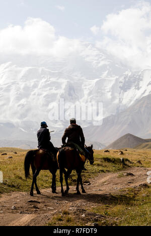 Tulpar, Kyrgyzstan August 21 2018: Two Kyrgyz riders ride their horses to base camp at the foot of Peak Lenin in Kyrgyzstan - Stock Photo