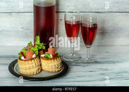 French cuisine, crunchy patties with lettuce and smoked salmon on a bright, rustic background, next to a glass of red wine - Stock Photo