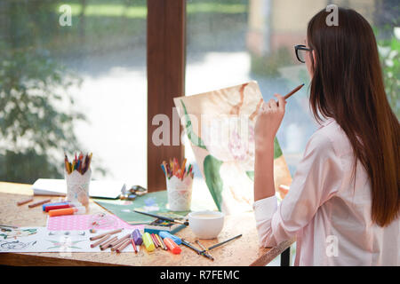Young artist looking at her picture of flower and thinking. Unrecognizable woman holding pencil in hand. Girl sitting at table with painter's supplies as markers, brushes and sheets of paper. - Stock Photo