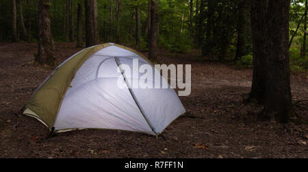 Dark forest with a single nylon tent set up - Stock Photo
