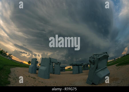 Nebraska tourist attraction 'Carhenge' with a thunderstorm in the background. Frmed from vintage American automobiles, all covered with grey paint. - Stock Photo