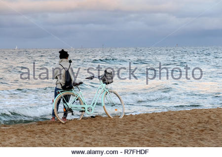 A woman leaning on a bicycle is looking at the sea - Stock Photo