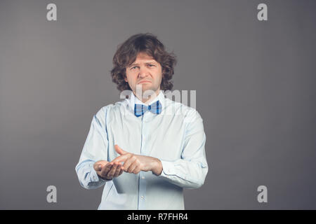 Man in shirt and tie shows outstretched hand with open palm, index finger pointing at palm. Upset man asks for money. Lack of money concept. Asking for help, financial assistance. Financial meltdown - Stock Photo