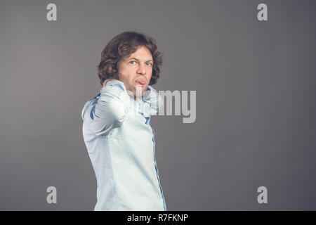 Man in shirt and bow tie with wavy hair on a grey background smiles and shows humorously the tongue. Standing half-turned male stuck his tongue right into the camera. Horizontal. Isolated. Copy space - Stock Photo