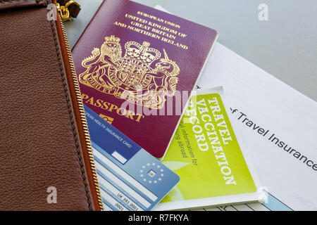 Essential travel documents for travelling abroad British biometric passport EHIC card vaccination record and travel insurance with a wallet England UK - Stock Photo