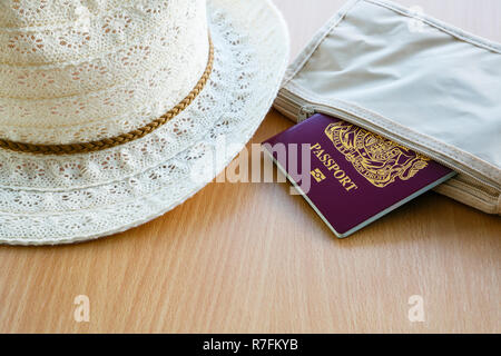 Travel things for travelling abroad British biometric passport in a wallet with lady's sunhat on a table top. England, UK, Britain - Stock Photo