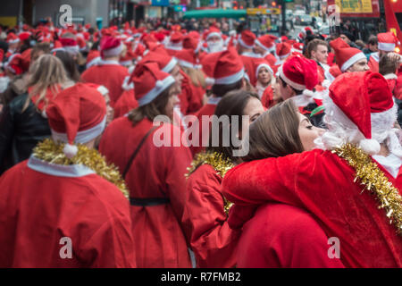 London, UK - December 2018 : Men and woman dressed in santa outfits kissing and hugging each other while taking part in a themed SantaCon event - Stock Photo