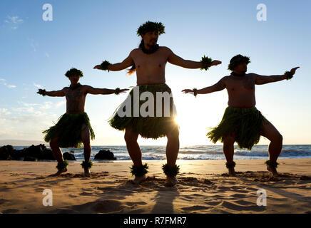 Three male hula dancers at sunset at Maui, Hawaii. - Stock Photo
