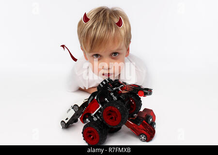 Naughty or good child for Christmas? PF or letter to Santa-Claus for Christmas. Little child boy appearing as an adorable angelic devil - Stock Photo