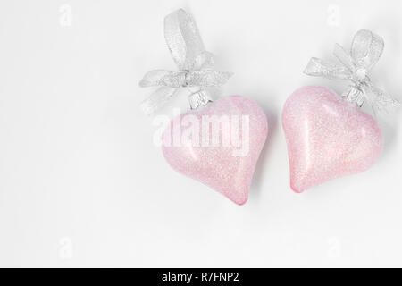 Pink, Christmas baubles in the shape of a heart on a white background. - Stock Photo
