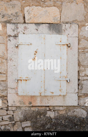 Very old closed window with white wooden shutters. Window with stone frame on a stone house. - Stock Photo