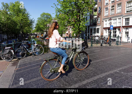 Woman cycling in Amsterdam, Netherlands - Stock Photo