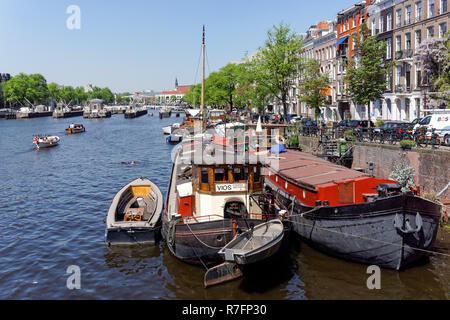 Boats on the river Amstel in Amsterdam, Netherlands - Stock Photo