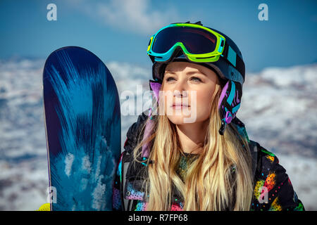 Portrait of a beautiful blond woman with snowboard standing in the snowy mountains, sportive wintertime activity - Stock Photo