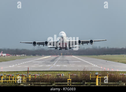 GATWICK AIRPORT, ENGLAND, UK – DECEMBER 09 2018: View directly down the runway as an Emirates Airline plane takes off from London Gatwick Airport - Stock Photo