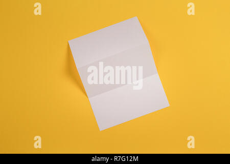 Mockup of blank white tri fold booklet brochure on yellow background - Stock Photo